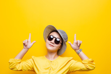 Portrait woman wearing sunglasses and hat point up to copy space isolated over yellow background