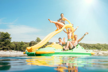 Little girl sliding down into sea water from  floating Playground slide Catamaran as she enjoying sea trip with her sister and brother