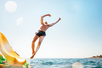 Man jumping backwards somersault into the sea. Happy beach vacation concept image.