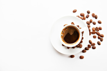 Coffee cup with roasted brown beans scattered on white table with a lot copy space for text. Flat lay composition. Close up, top view, background.