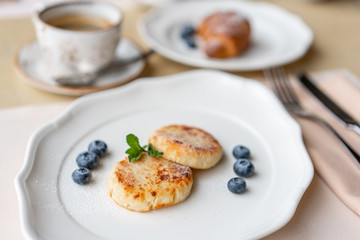 Cottage cheese pancakes or syrniki with blueberry on white plate, closeup view. Russian, Ukrainian cuisine. Healthy tasty breakfast