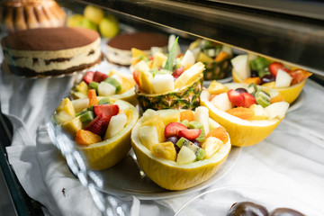 Dessert of fresh fruit.. Showcase desserts in an Italian cafe or trattoria. Variety of cakes on display.
