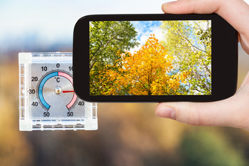 thermometer on home window and trees in autumn