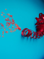 red glitter on pastel colored background. Minimalist still life photography concept.