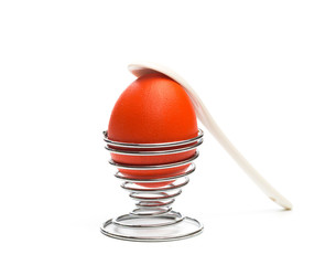 easter egg in egg stand  with spoon isolated