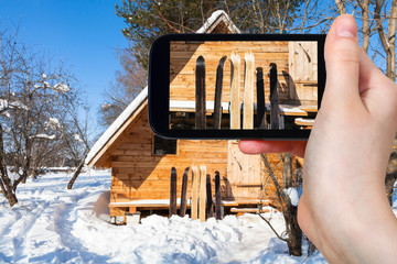 wide forest skis in front of wooden cottage