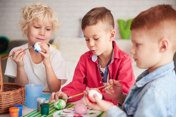Group of boys painting easter eggs