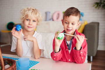Two happy boys painting eggs for easter time