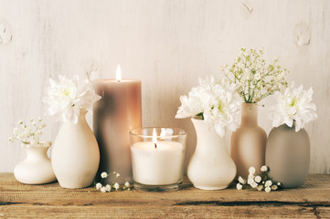 White flowers in neutral colored vases and candles