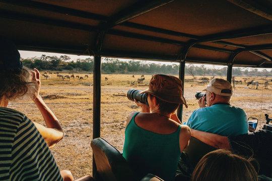 Touristen fotografieren Zebras während eines Gamedrives, Makgadikgadi Pans Nationalpark, Botswana