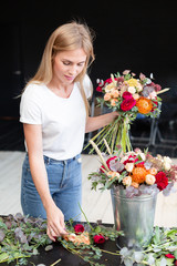 Florist workplace. Woman arranging a bouquet with roses, chrysanthemum, carnation and other flowers. A student of floristry in master classes or courses