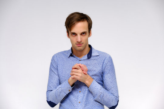 Concept studio portrait of a handsome young man isolated on a white background with different emotions in a blue shirt