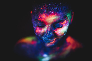 Portrait of a girl painted in fluorescent UV colors.