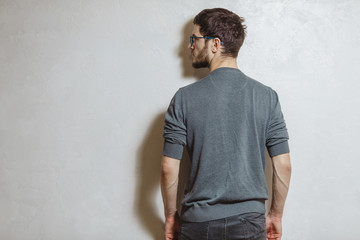Back view of young man, over white textured background.