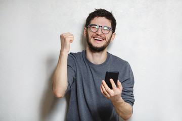 Portrait of young happy man using smartphone, over white textured background.