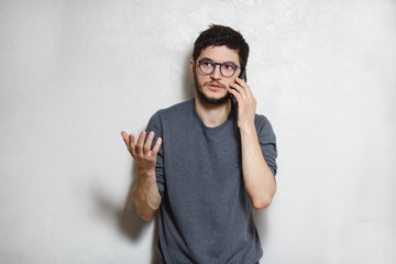 Portrait of young man talking on the phone, over white textured background.