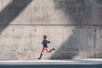 Muscular Male athlete sprinter running fast,exercising outdoors,jogging outside against gray concret background with copy space area for text message or ad content.Side view,full length Wall mural