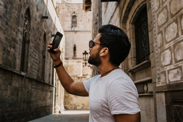 Content attractive hispanic man in white tshirt photographing himself on mobile phone while enjoying city travel.Bearded hipster male making selfie via smartphone on gotic streets