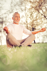 Cheerful mature man enjoying meditation in park