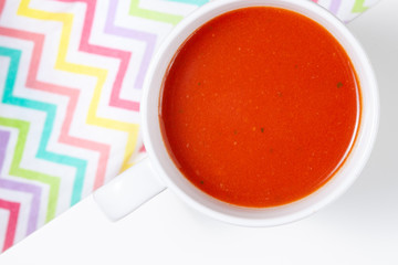 Bowl of tomato soup isolated on white background with shadows, top view