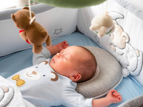 Close-up portrait cute little mixed race Asian and Caucasian baby son sleeping on back. Daytime sleeping. Family, healthy with Baby Pillow for Newborn Breathable Protection for Flat Head Syndrome