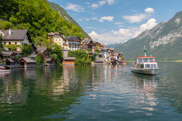 Tourists lake cruise boat on Hallstattersee by the World Heritage lakeside town in the Alps, Hallstatt, Salzkammergut, Austria.