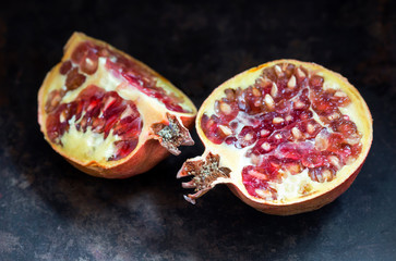 Pomegranate red sweet fruits, overriped on metal background