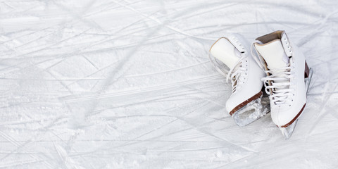 close up of figure skates and copy space over ice background with marks from skating or hockey