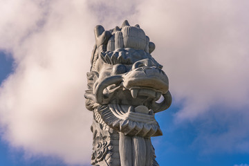 Close-up on the stone dragon head of the pillars that greet cruise ship visitors close to the Naha Port Cruise Terminal dock, symbol of sister cities Naha and Fuzhou in China.
