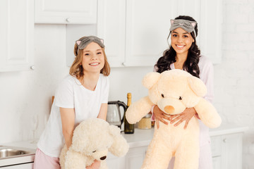 beautiful multicultural girls with teddy bears looking at camera during  pajama party at home b604d04af