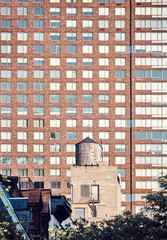 Water tank with a building in background, color toning applied, New York, USA.