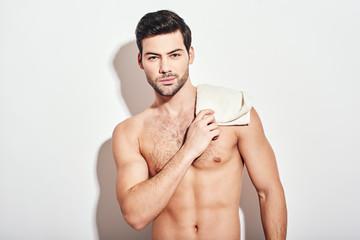 8d98b3ea14da Handsome man standing shirtless holding white towel