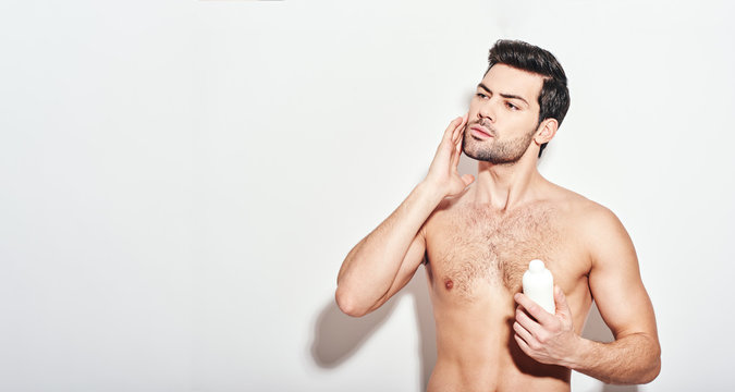 Another beauty treatment. Handsome man applies the moisturizer standing isolated over white background