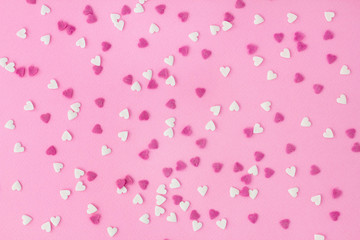 Small white and pink candy hearts, closeup on a pink background for wallpaper, card, invitation or poster