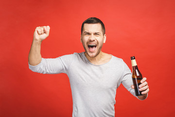 A young guy with a beard isolated on a red background holds a bottle of beer. Watching football match.