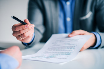 Businessman offering pen to other businessman for signing contract or document.