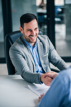 Friendly business handshake. Smiling handsome elegant man handshaking with employee.