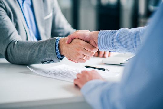 Businessmen handshaking over signed contract.