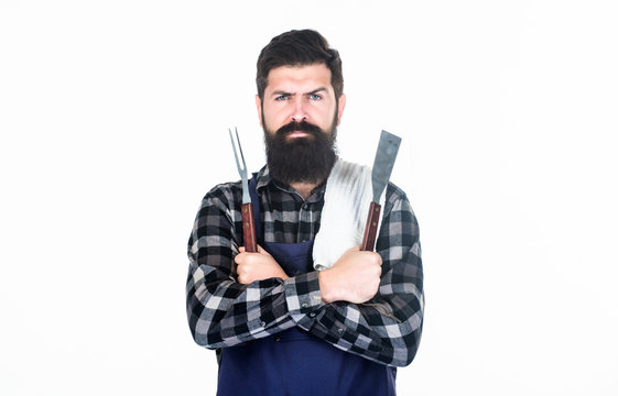 Roasting and grilling food. Man hold cooking utensils barbecue. Tools for roasting meat outdoors. Picnic and barbecue. Cooking meat in park. Masculine hobby. Bearded hipster wear apron for barbecue