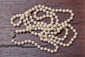 Beautifull pearl necklace on textured wooden block