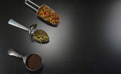 three tea spoons with real tea on a black wooden background