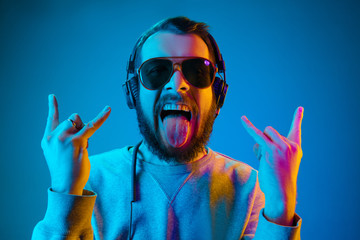 Photo sur Aluminium Magasin de musique Enjoying his favorite music. Happy young stylish man in sunglasses with headphones listening sound and smiling while standing against blue neon background