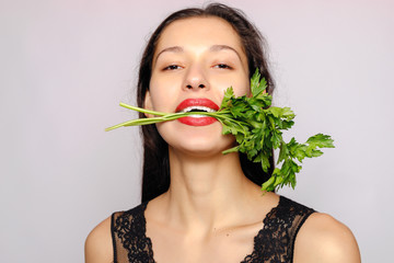Beautiful smiling girl with parsley. Photo of fashion female on gray background. Close up. Healthy lifestyle concept. Parsley contains many vitamins.