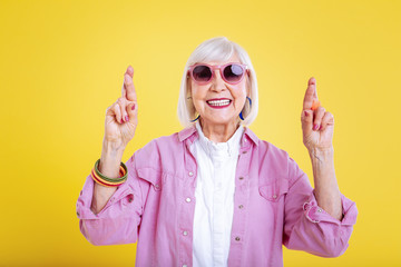 Stylish modern retired woman with bright manicure having fingers crossed
