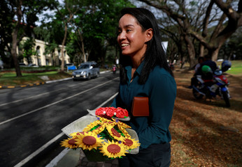 Filipino lawyer and entrepreneur Alex Castro holds bouquets of origami flowers to delivered to clients in Quezon City