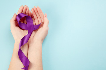 International or world Epilepsy Day concept. The text and a purple ribbon with female hands on a white wooden table background. The health, breast, awareness, campaign, disease, help, care, support