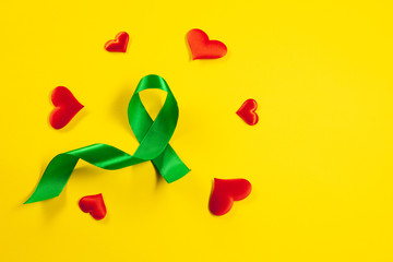 Liver Cancer and Hepatitis B - HVB Awareness month ribbon, Emerald Green or Jade ribbon awareness color on yellow background. The cancer, health, help, care, support, hope, illness, survivor