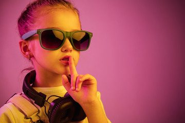 Neon portrait of young girl with headphones enjoying music and calling for silence. Lifestyle of young people, human emotions, childhood, happiness concept.