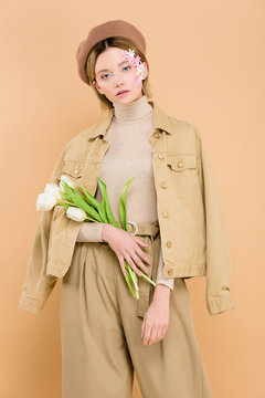 trendy woman in beret holding bouquet of flowers isolated on beige