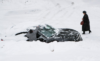 A man cleans a car from snow during a snowfall in Moscow
